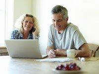 Pareja sentada en la mesa con su computador portátil - Preguntas y respuestas sobre el periodo de inscripcion abierta a Medicare