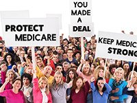 Multitud con pancartas en acto cívico.