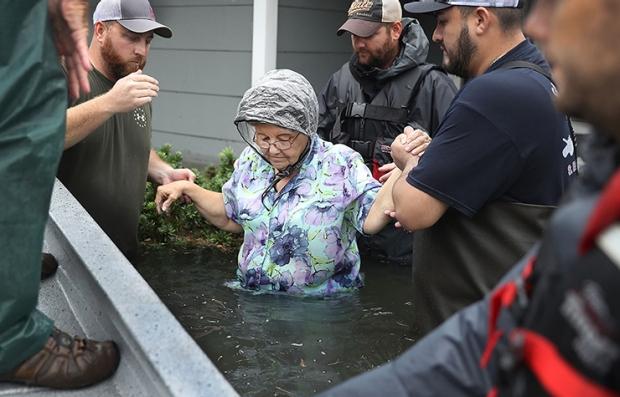 Brigada de rescate socorriendo a una anciana en medio de un desastre natural