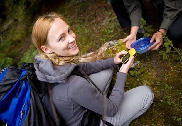 Young woman with GPS finds geocache, Hunt for Treasure, Have Fun with Your Family & Friends This Summer (Montgomery Martin/Alamy)