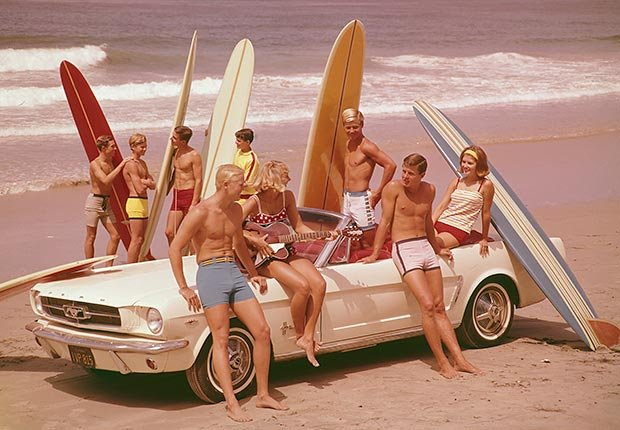 Bañistas en la playa con tablas de surf y Ford Mustang convertible - Carros clásicos de antes y de ahora