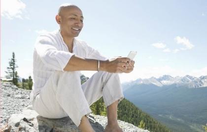 Hombre sonriendo con un teléfono inteligente en cima de una montaña, Consejos de teléfonos inteligentes para los Viajeros
