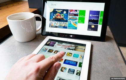 Man using iPad and Microsoft Surface. Digital tablet buying guide. (Iain Masterson/Alamy)