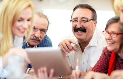 Adultos mayores observan una tableta electrónica