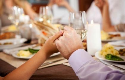 Pareja tomada de la mano en la mesa - Cómo preparar su casa para las fiestas