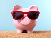 Pink piggy bank on a beach with red sunglasses, Warm weather is linked with spending more.