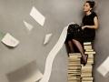 Mujer sentada en una columna de libros apilados - Cómo auto pubiclar un libro usando la tecnología.