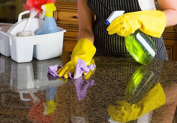 Mujer con guantes limpiando superficie de granito - Evita reparaciones costosas en el hogar