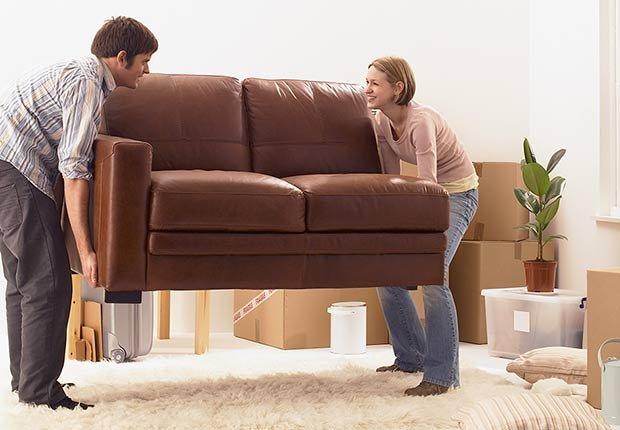 Hombre y mujer moviendo un sofá encima de un tapete - Evita reparaciones costosas en el hogar