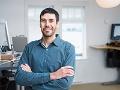 Un hombre cruzado de brazos y sonriendo en una oficina.