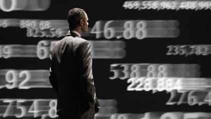 Un hombre de pie delante de un muro de números móviles