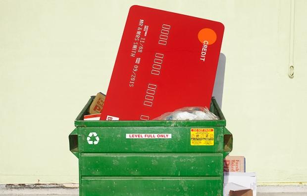 Una tarjeta de crédito gigante sobre un basurero de reciclaje y aprende a manejar tus deudas.