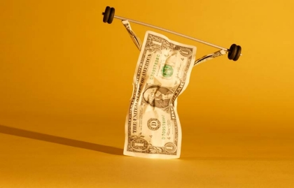 Un billete de dolar levantando pesas - Considere la posibilidad de