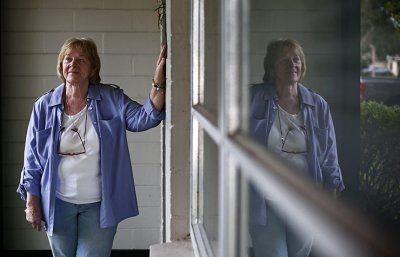Deanna Falls stands outside the house she and her husband almost lost to a convincing scam.