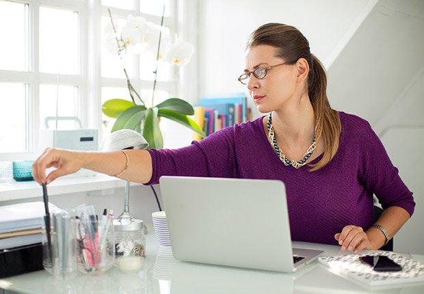 Mujer frente a un computador en su casa - Deducción de impuestos, gastos búsqueda de trabajo