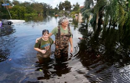 Un hombre y una mujer caminando sobre las inundaciones dejadas por el huracán Irma