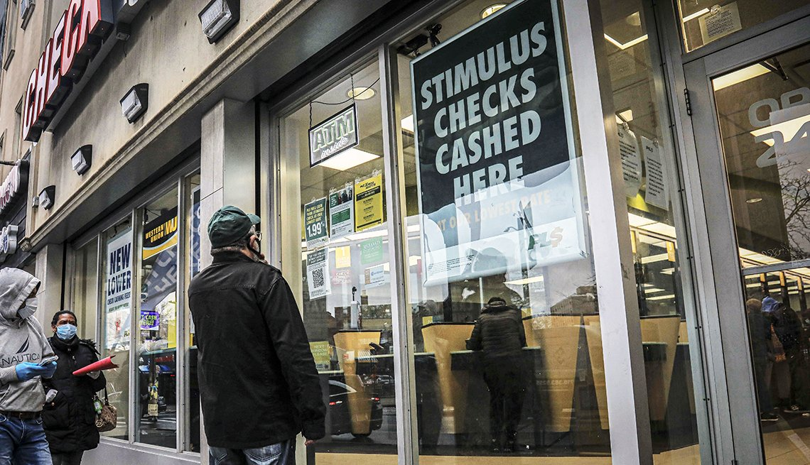 people wearing face masks due to COVID-19 wait outside a stimulus check cashing service center in Brooklyn New York.