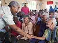 Barry Rand shakes hand with a seated woman at the St. Vincent de Paul nursing home in Leogane where children put on a show for the elderly, Barry Rand visits Haiti