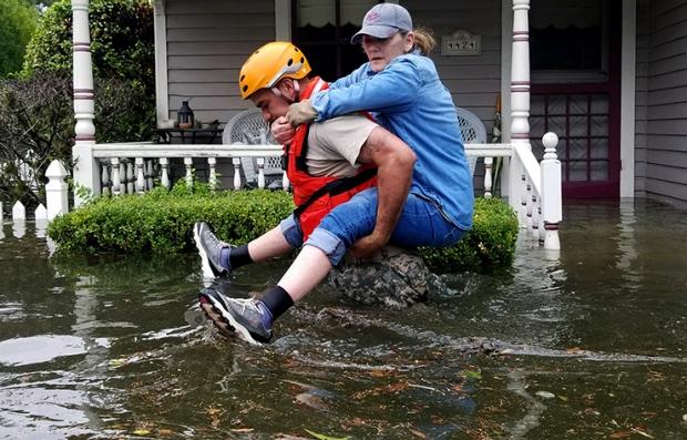 Mujer siendo rescatada de una inundación