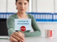 Las leyes de identificación puede restringir los votantes mayores, mujer en una oficina que sostiene un pequeño aviso que dice - Se requiere identificación del votante