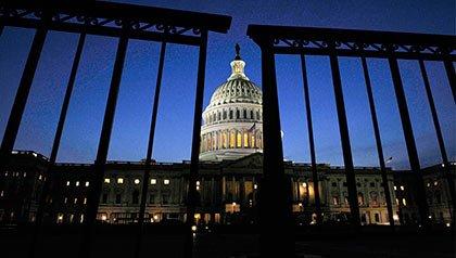 El edificio del Capitolio de EE.UU. ve a través de una cerca en la noche. Cómo un cierre del gobierno podría afectarlo.