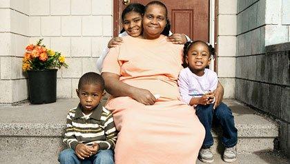 Abuela con sus tres nietos posando afuera de su casa