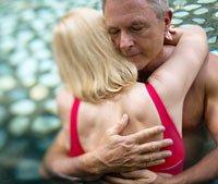 Pareja que se abraza en uns piscina - El sexo es saludable para los hombres mayores