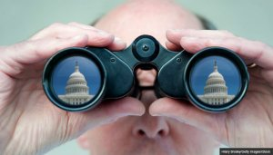 Man with binoculars watching the U.S. capitol - AARP Government Watch