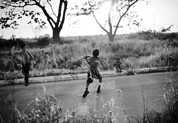 Niño jugando béisbol en un parque