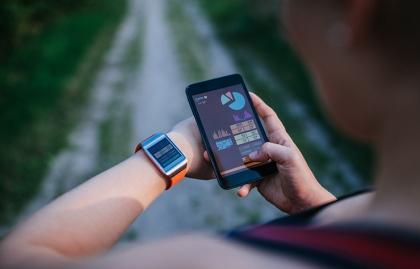 Mujer sincronizando su reloj y teléfono inteligente - Qué pueden hacer por ti las pulseras y los relojes inteligentes