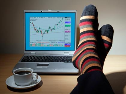 feet up on a desk with coffee cup and laptop