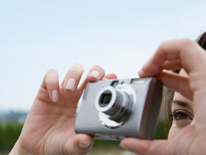 woman taking picture with digital camera