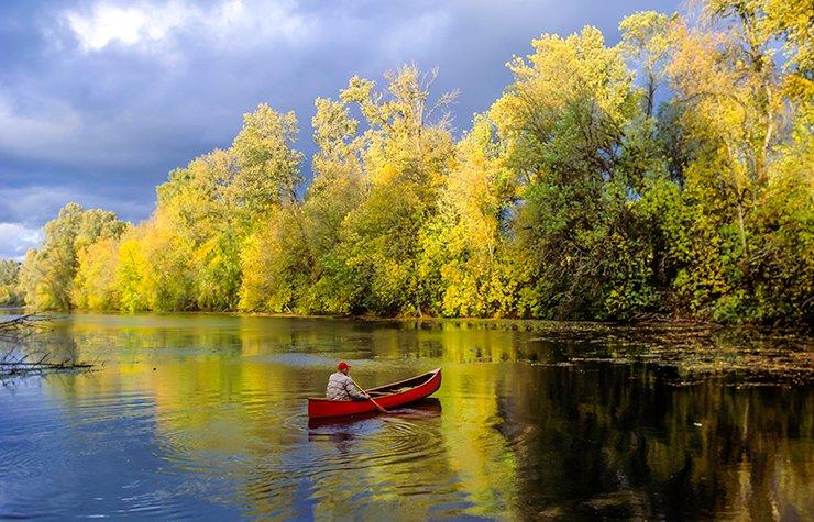 Ciudades para divertirse al aire libre - Hombre en kayak por un río