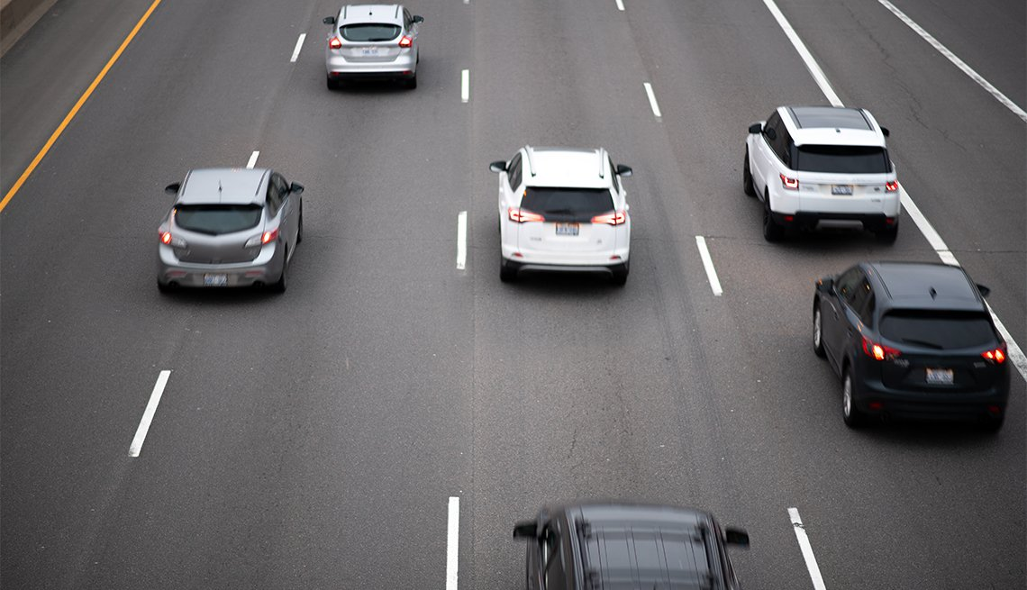 Cars travel in a pack on a major highway / interstate.