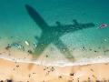 Estrategias para conseguir descuentos en viajes de último minuto - Sombra de avión pasando sobre el mar