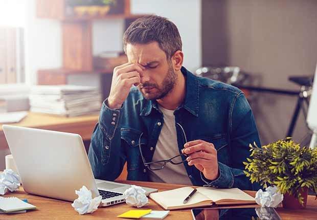 Trabajos con poco estrés, pero bien pagados, hombre frente a un computador y tocándose la cara