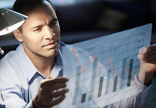 Trabajos con poco estrés, pero bien pagados, un economista mirando un gráfica con datos