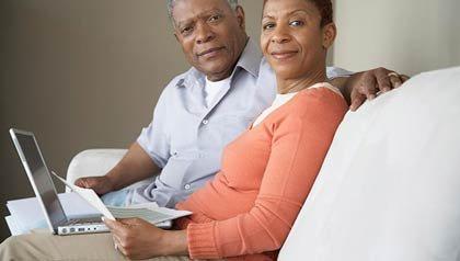 Pareja usando la computadora portátil - ¿Cree usted que está ahorrando lo suficiente para la jubilación?