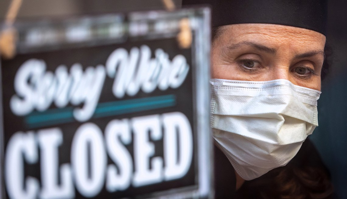 A woman in a mask stands next to a sign that says sorry we're closed