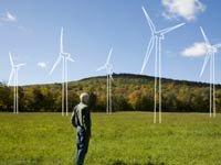 Empleos ecológicos - Hombre mirando un campo de turbinas de viento.