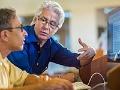 Hombre adulto aconsejando a otro que está sentado frente a un computador - Asesor de cambio de carrera
