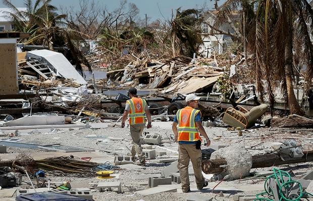 Hombres caminando por escombros dejados por el paso del huracán y los empleos a los que podrían aplicar las personas mayores.