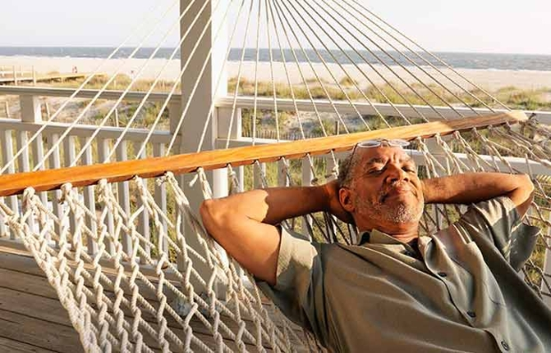 Mature adult relaxing on hammock, Take that vacation that will boost your career