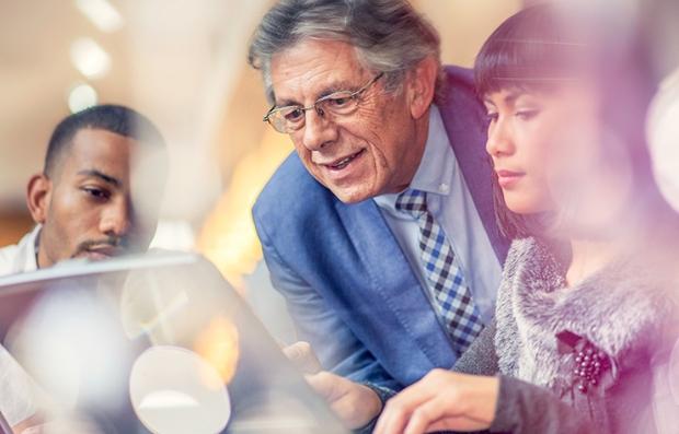 Hombre mayor asesorando a dos personas más jóvenes, jubilarse a tiempo parcial es normal hoy en día
