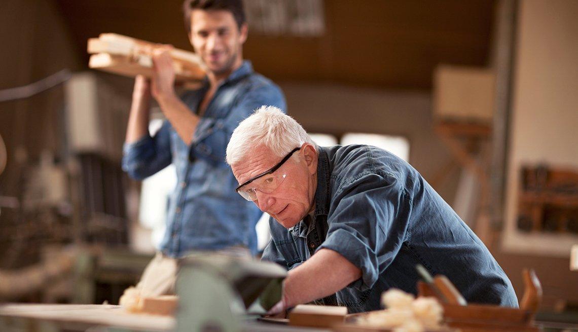 Un hombre joven y otro mayor trabajando en una carpintería, cambios del Seguro Social para el 2017