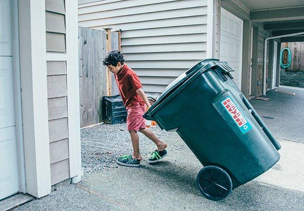 Claves para mantener tu casa segura cuando estás lejos - Adolescente arrastra una caneca de basura