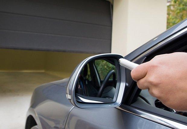 Claves para mantener tu casa segura cuando estás lejos -  Persona usa el control remoto para abrir la puerta del garaje