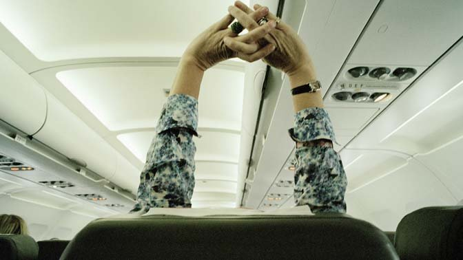 Stay healthy on a plane by stretching, even if you're seated.
